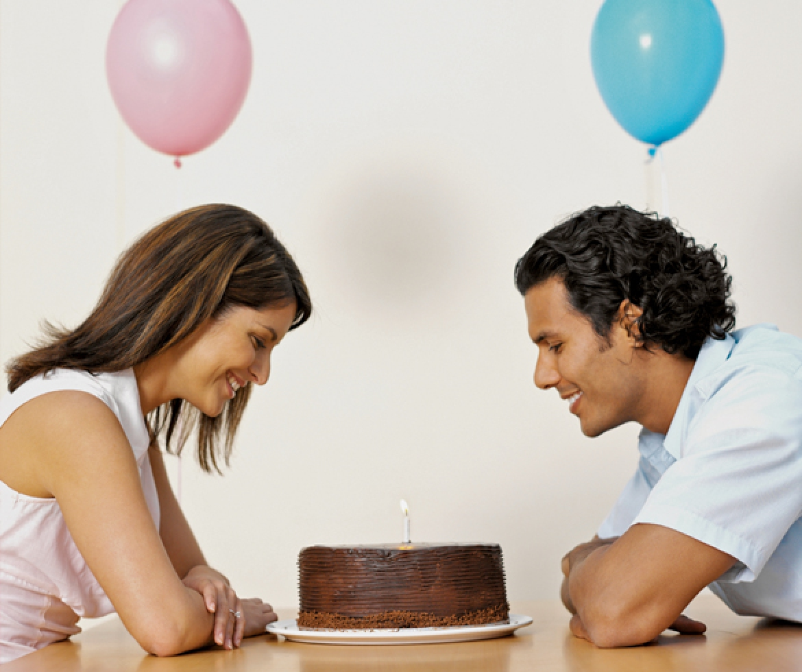 Man and woman staring at a chocolate cake with blue and pink balloons.