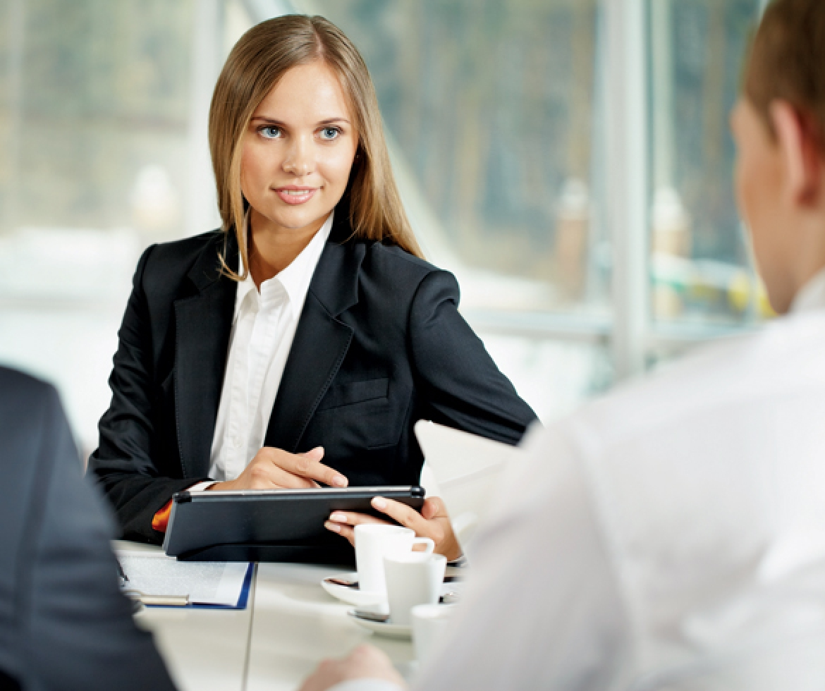 Woman in business attire sitting across from man in a meeting - 11140