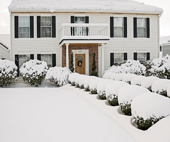 Home with snow covered lawn.