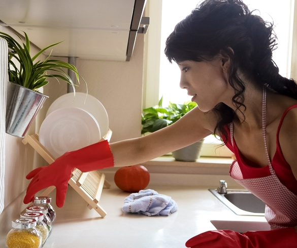 Woman cleaning a kitchen using rubber gloves and an apron.