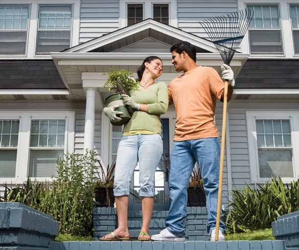 Man and woman holding garden tools and plants standing outside of a house.