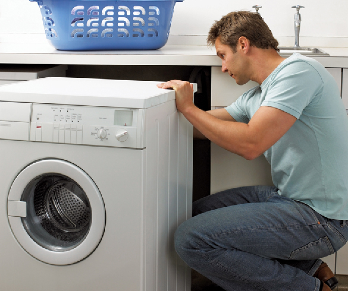 Man working on a laundry appliance.