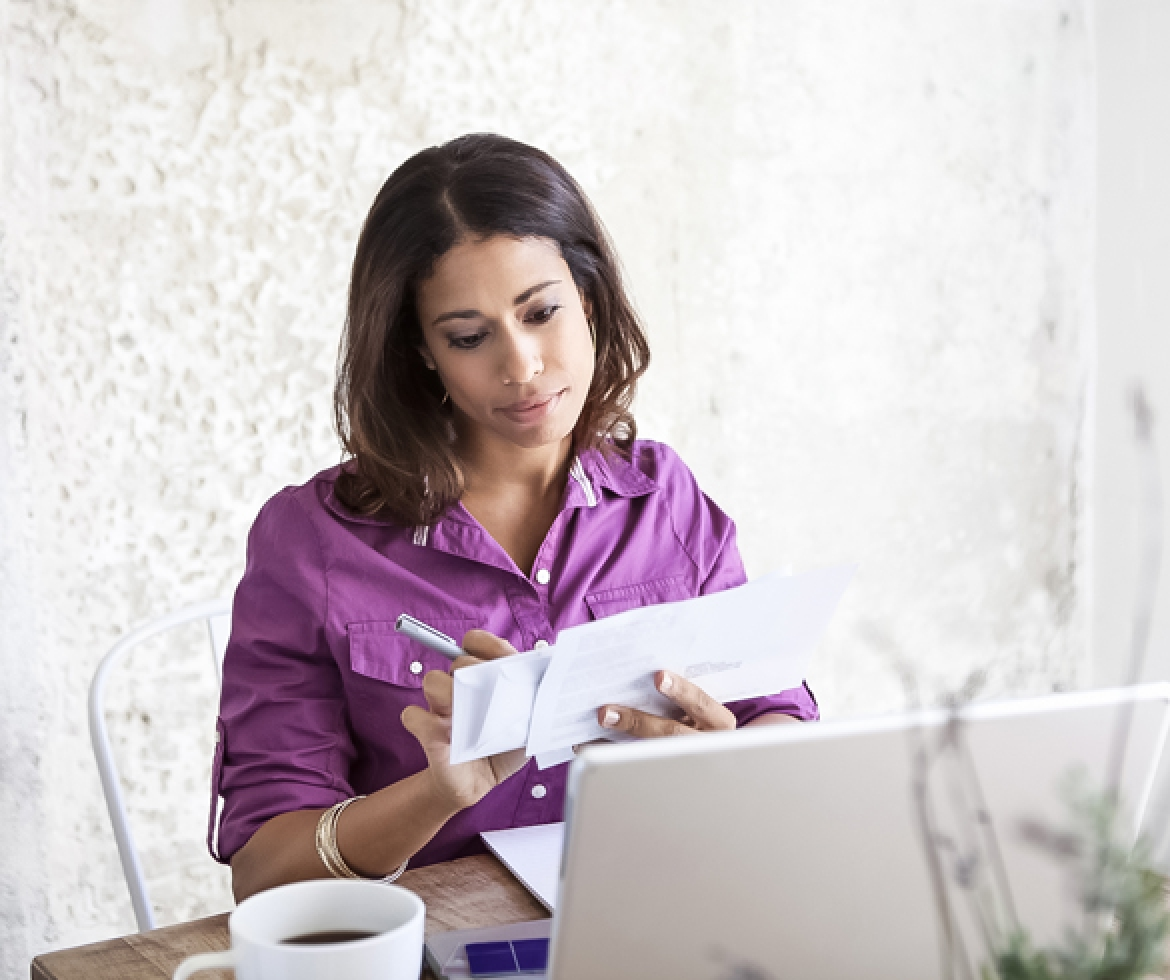 Woman viewing paperwork while sitting at laptop - 12815