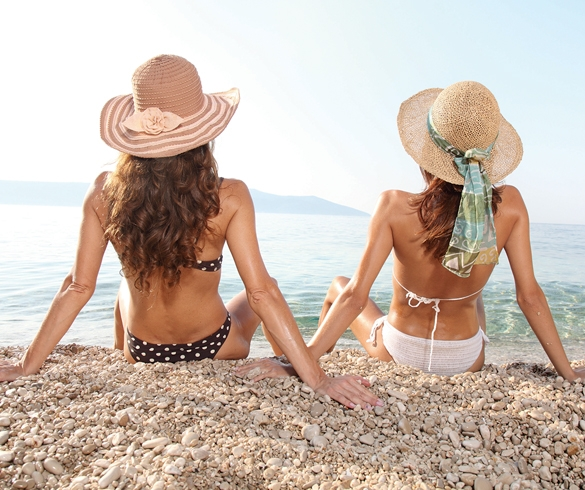 Two women sitting on a beach shore tanning - 13137