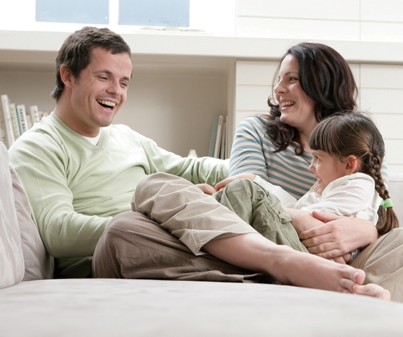 Man, woman and child sitting on couch laughing - 12762